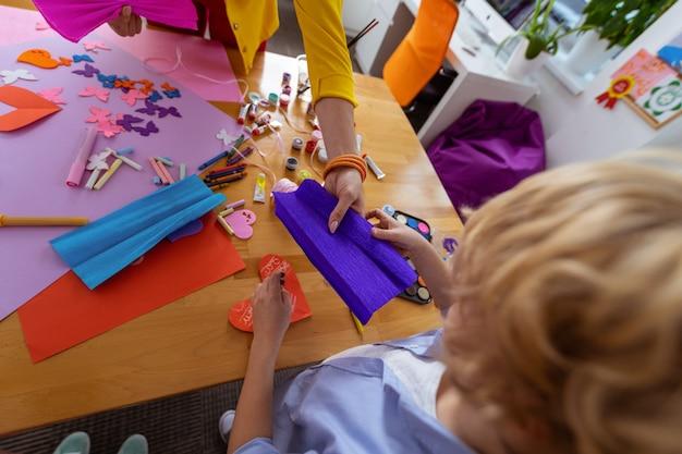 Blaues papier geben. lehrer, der blaues papier für schüler gibt, während er im unterricht angewendete ornamente herstellt