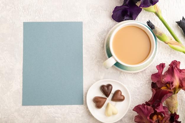 Blaues papierblatt mit tasse cioffee, schokoladenviolett und burgunder irisblumen auf grau.