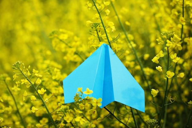 Blaues papierflugzeug auf gelbem hintergrund.