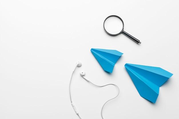 Blaues papierflugzeug mit lupe