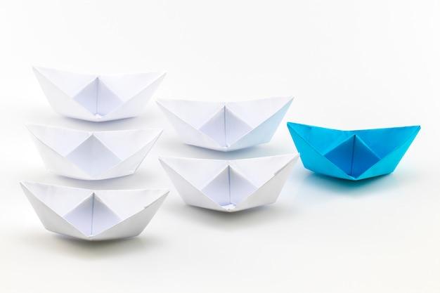 Blaues papierschiff, das unter weißen papierschiffen führt