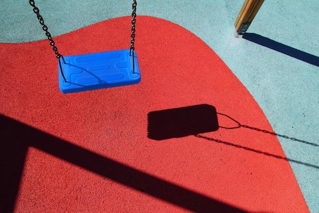 Blaues parkschwingen oder kinderspielplatz des roten bodens