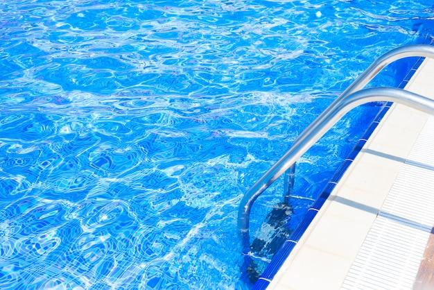 Blaues pool mit treppe am hellen sommertag