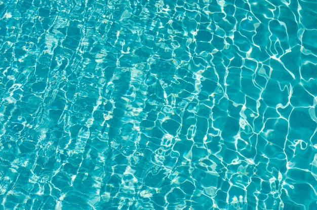 Blaues poolwasser mit sonnenreflexionen