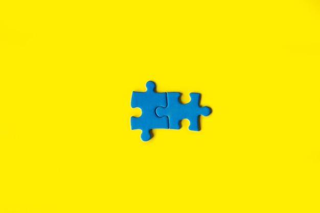 Blaues puzzle auf gelbem hintergrund, geschäftsverbindung, erfolgs- und strategiekonzept, teamarbeit