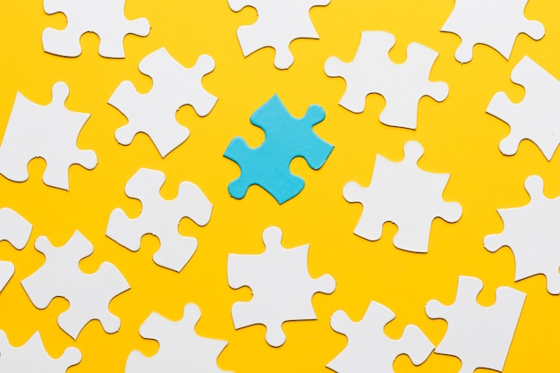 Blaues puzzlespiel mit weißem puzzlestück auf gelbem hintergrund
