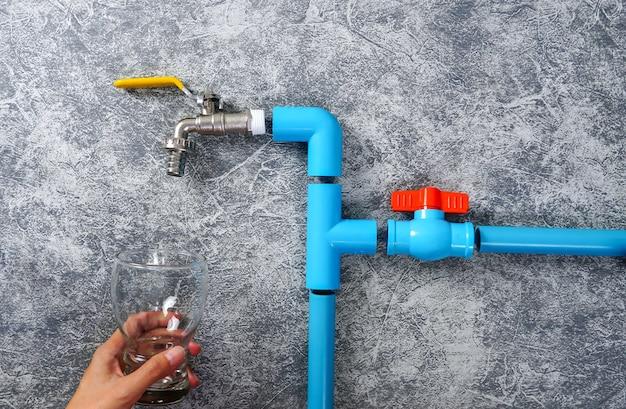 Blaues pvc-rohr mit wasserhahn und wasserventil mit kopierraum ein glas wasser in der hand