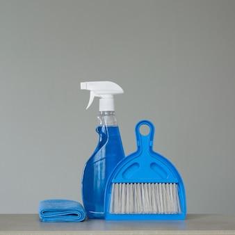 Blaues reinigungsset auf neutraler oberfläche: reinigungsmittel, staubtücher, schaufel und besen einsprühen.