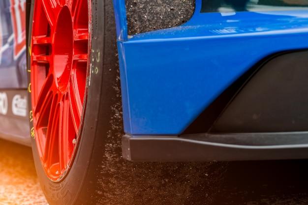 Blaues rennauto mit hochleistungssportrad und -reifen.