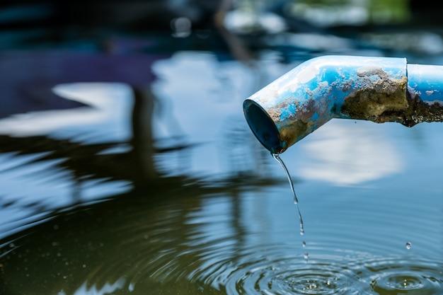 Blaues rohr ein wassertropfen des teichs mit kräuselung