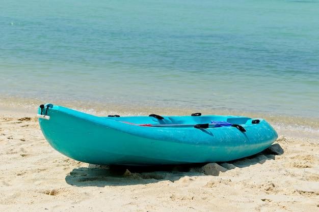 Blaues ruderboot am strand mit dem schönen ozean im hintergrund
