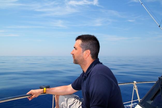 Blaues ruhiges ozeanwasser des seemannmann-segelboots