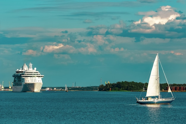 Blaues segelboot, das gegen das kreuzfahrtschiff in riga reist