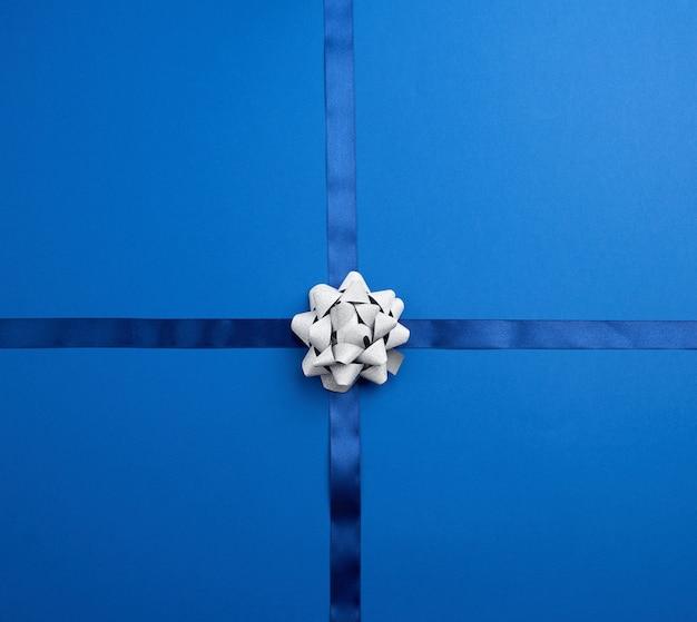 Blaues seidenband gekreuzt auf dunkelblauem, in der mitte silbernem band