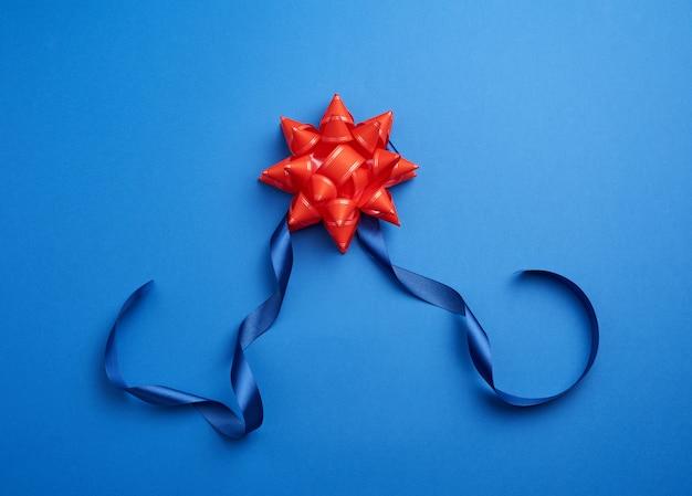 Blaues silk dünnes band verdreht und roter glänzender bogen auf einem blau