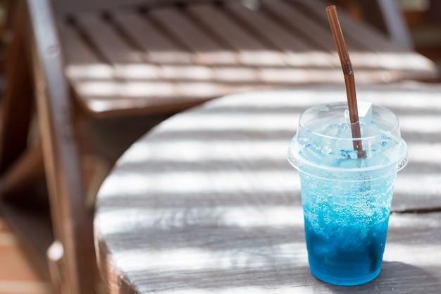 Blaues soda in einem plastikglas gesetzt auf einen holztisch
