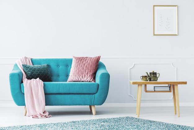 Blaues sofa mit pastellrosa decke und zwei kissen im hellen wohnzimmer mit wandleisten