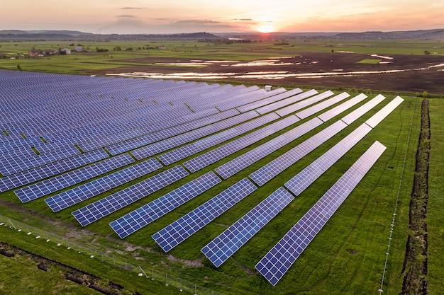 Blaues solar-foto-voltaik-panelsystem, das erneuerbare saubere energie auf ländlicher landschaft und untergehenden sonnenhintergrund erzeugt.
