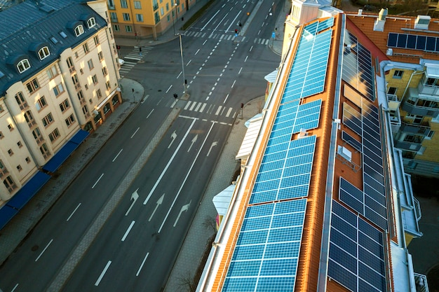 Blaues solarfoto voltaic panelsystem auf der hohen wohngebäudedachspitze am sonnigen tag