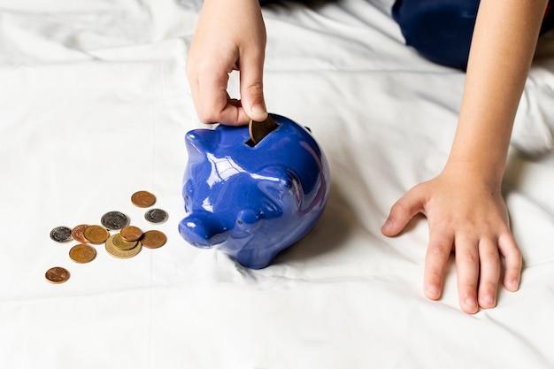 Blaues sparschwein gefüllt mit münzen