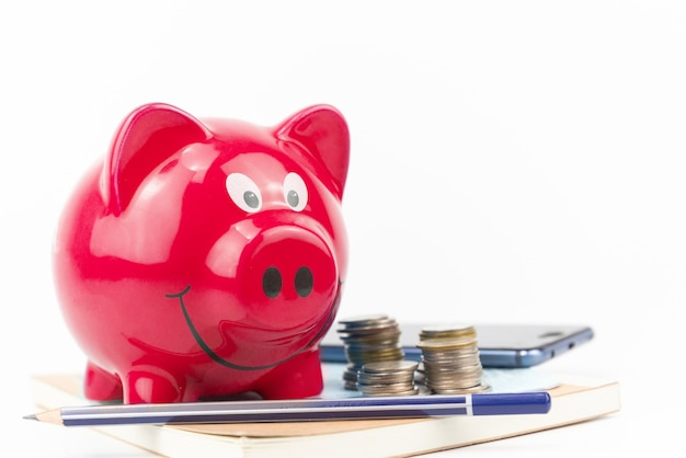 Blaues sparschwein mit münzenstapel auf kontobuch auf weiß