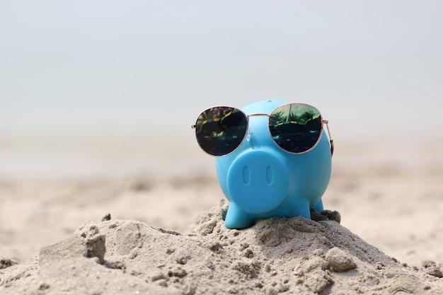 Blaues sparschwein mit sonnenbrille auf seestrand