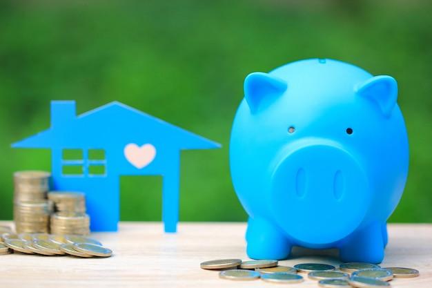 Blaues sparschwein und stapel münzengeld mit blauem hausmodell