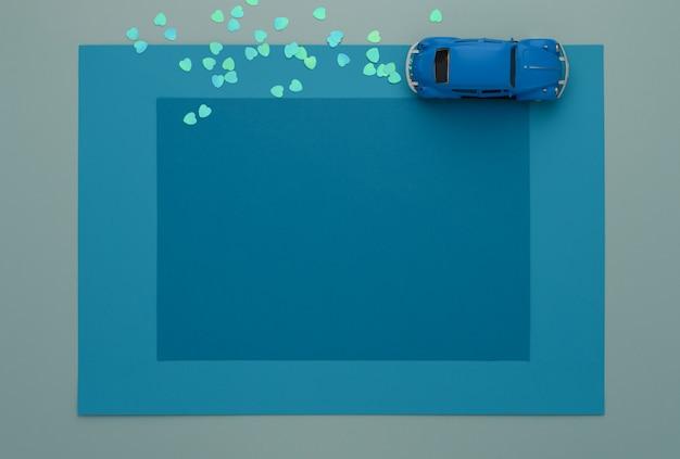 Blaues spielzeugauto auf einigen schichten gestalten hintergrund des blauen papiers.