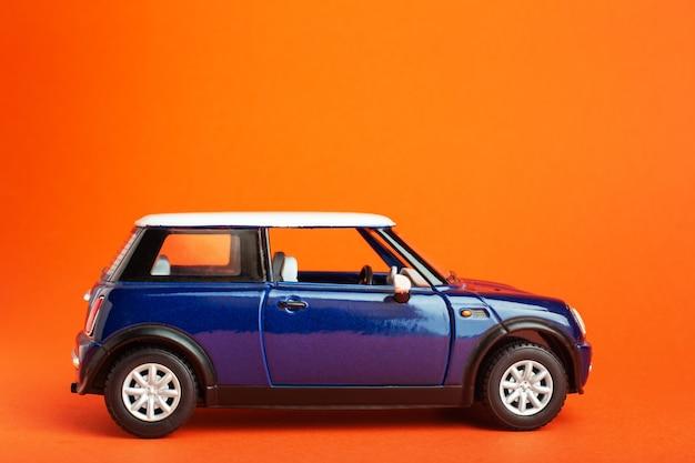Blaues spielzeugautomodell auf farbe orange hintergrund reiseauto transportkonzept urlaubsreise abenteuer...