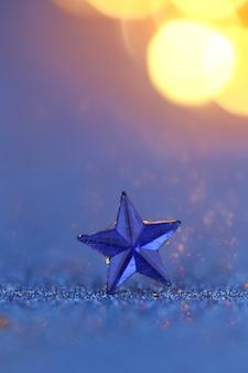 Blaues sternmakro auf einem blauen funkelnhintergrund mit orange bokeh.