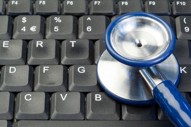 Blaues stethoskop auf tastatur