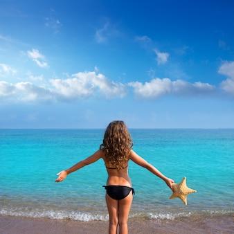 Blaues strandmädchen mit dem bikini, der hintere ansicht der seestern hält
