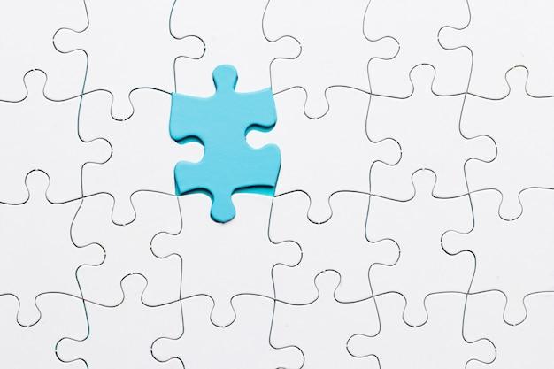 Blaues stückpuzzlespiel angeschlossen mit weißem stückhintergrund