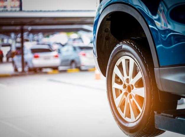 Blaues suv-auto mit dem hochleistungsreifen parkte an der werkstattgarage
