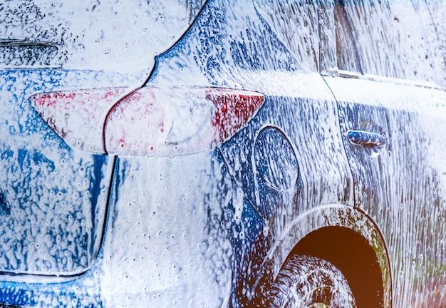 Blaues suv-auto mit sport und modernem design, das mit seife wäscht.