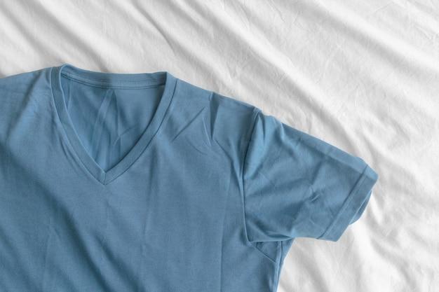 Blaues t-shirt liegt auf weißem bettlaken.