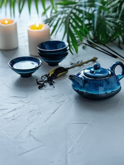 Blaues teeset für chinesische teezeremonie. brennende kerzen und duftende paare.