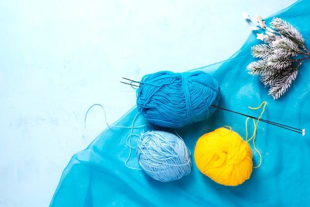 Blaues und gelbes garn auf blauer oberfläche neben schneebedeckten tannenzweigen.