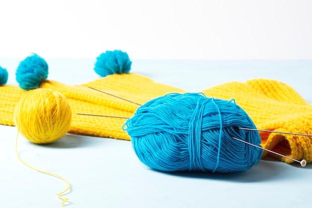 Blaues und gelbes garn liegt vor dem hintergrund eines gelben strickschals.