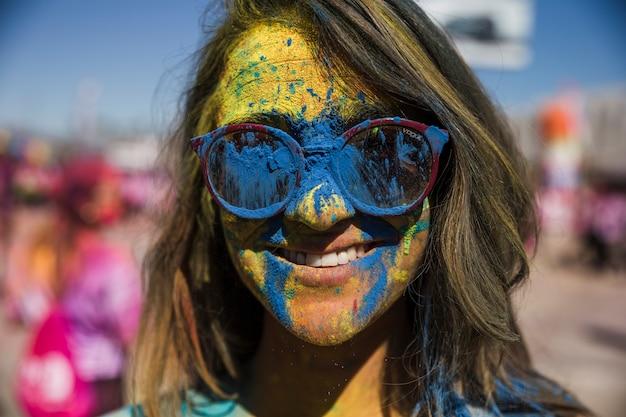 Blaues und gelbes holi farbpulver auf dem gesicht der frau