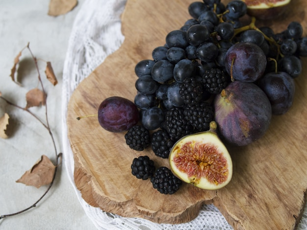 Blaues und lila essen. brombeeren, trauben, pflaumen, heidelbeeren. leckere und reife früchte und beeren. herbst arrangement von früchten.