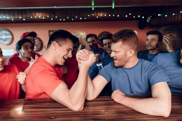 Blaues und rotes team lockert das armdrücken an der sportstange auf
