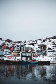 Blaues und weißes boot auf gewässern nahe weißen und braunen gebäuden während des tages