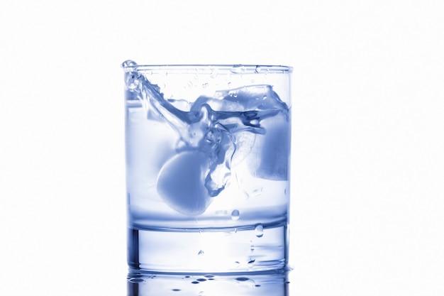 Blaues wasser, das aus einem glas mit tropfen heraus spritzt