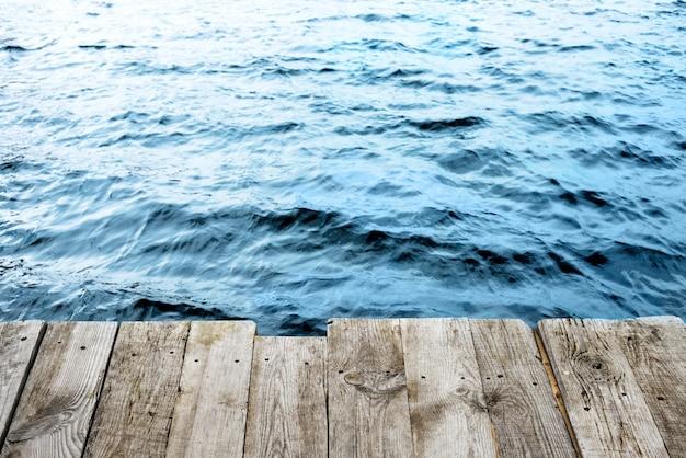 Blaues wasser mit leerer holzplattform. natürlicher hintergrund