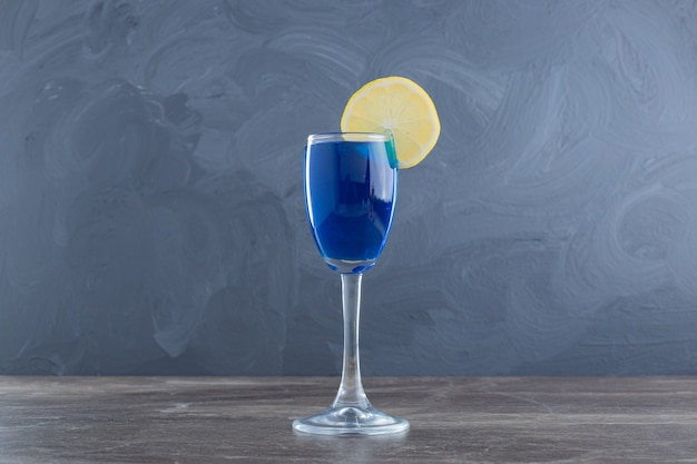 Blaues wasser mit zitrone auf marmortisch.