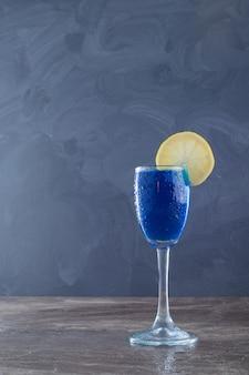 Blaues wasser mit zitrone auf marmorwand.