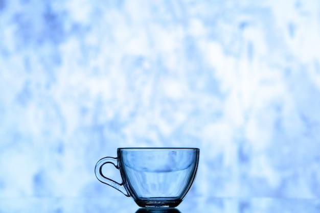 Blaues wasserglas der vorderansicht auf blau-weißem, verschwommenem hintergrundkopierraum
