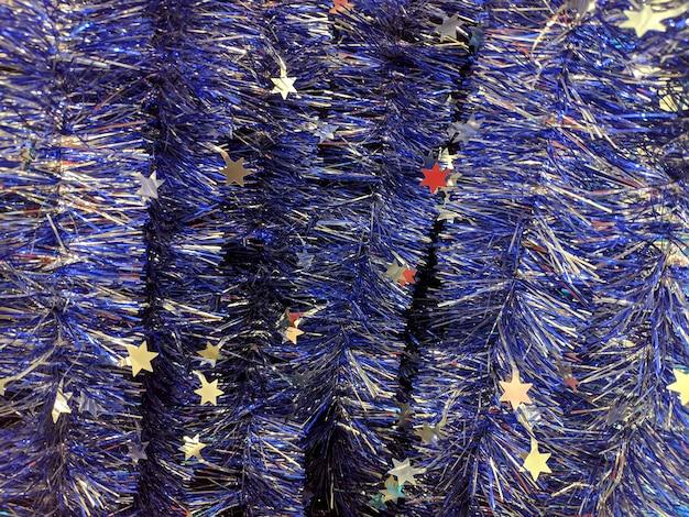 Blaues weihnachts-lametta. mehrfarbige dekorationen für die feier des neuen jahres. textur.