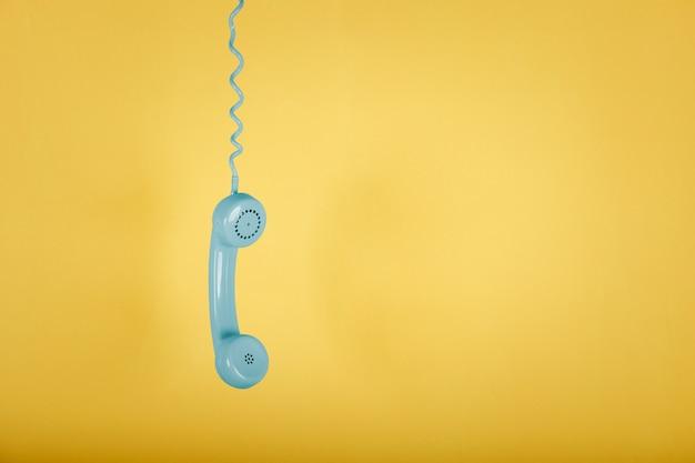Blaues weinlese-telefon, das auf gelbem raum hängt